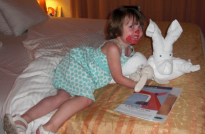 My daughter with her face painted like a clown posing with a bunny-shaped towel sculpture aboard a Carnival Cruise ~ Carnival Cruise Line with Kids