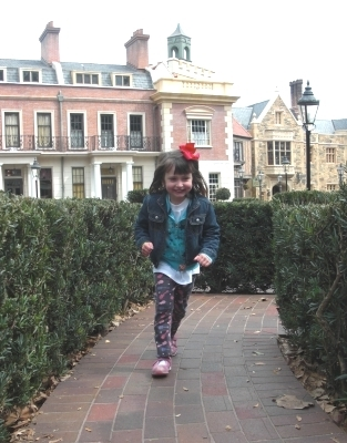 My daughter zipping through the United Kingdom Pavilion's hedge maze - Epcot