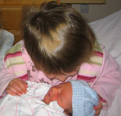 Big sister with her newborn baby brother
