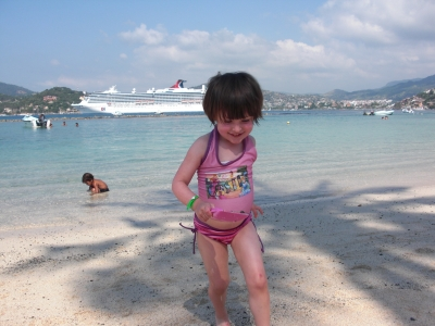 Playing on the shores of Las Gatas in Zihuatanejo, Mexico with a Carnival Cruise ship in the distance