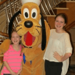 My tween and teen posing with Pluto aboard Disney Magic