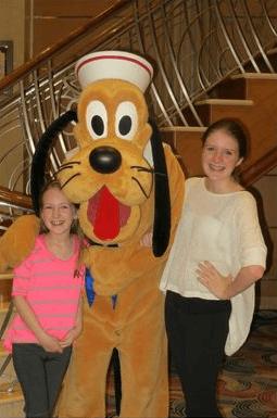 My tween and teen posing with Pluto aboard Disney Magic