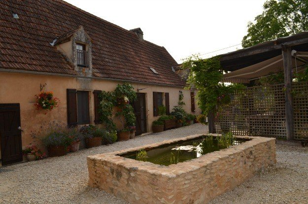 The courtyard and fish pond at Le Chevrefeuille, a bed and breakfast for families in Dordogne, France