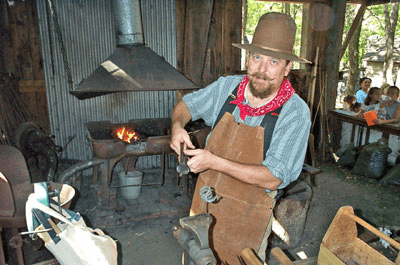 A blacksmith at Fort Worth Log Cabin Village (Photo from LogCabinVillage.org)