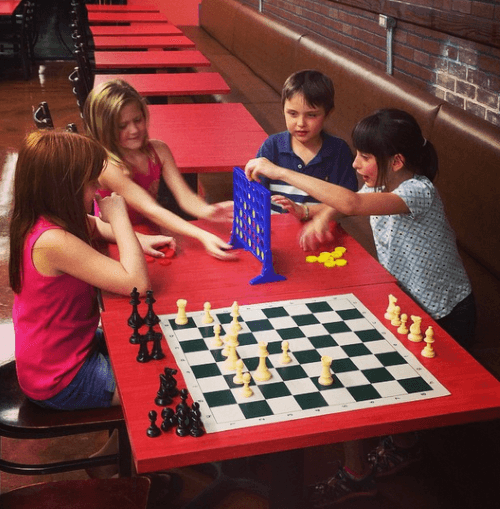 Playing games at an ice cream shop with her brother and friends after family dinner date