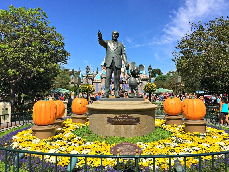 Pumpkins carved to depict beloved Disney characters surround the statue of Walt Disney at the end of Main Street