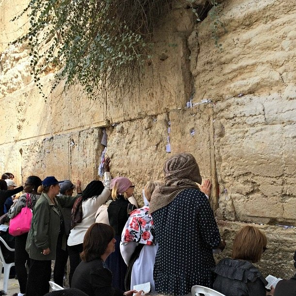 Women praying and placing notes in the Western Wall