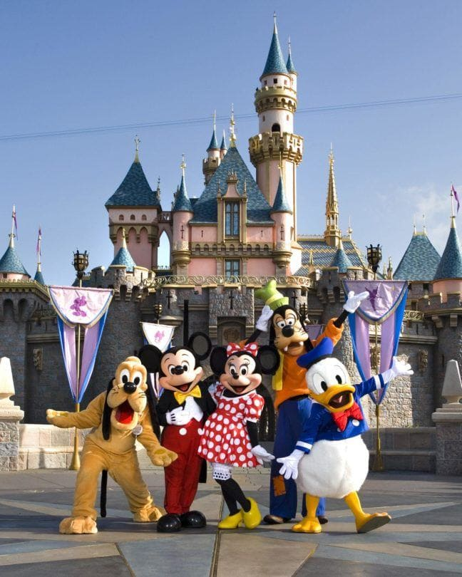 Classic Disney characters welcome visitors outside Sleeping Beauty Castle at Disneyland in Anaheim, California. Pluto, Mickey Mouse, Minnie Mouse, Goofy and Donald Duck