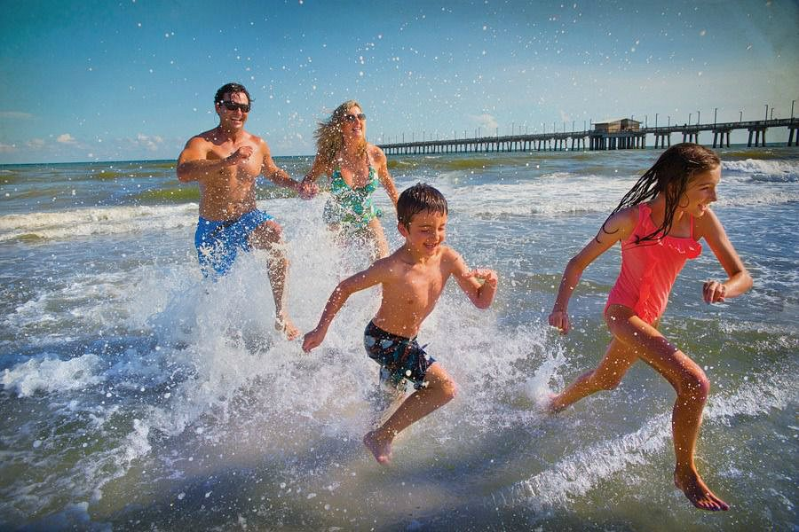 A family playing in the waves in Alabama's Gulf Shores with kids