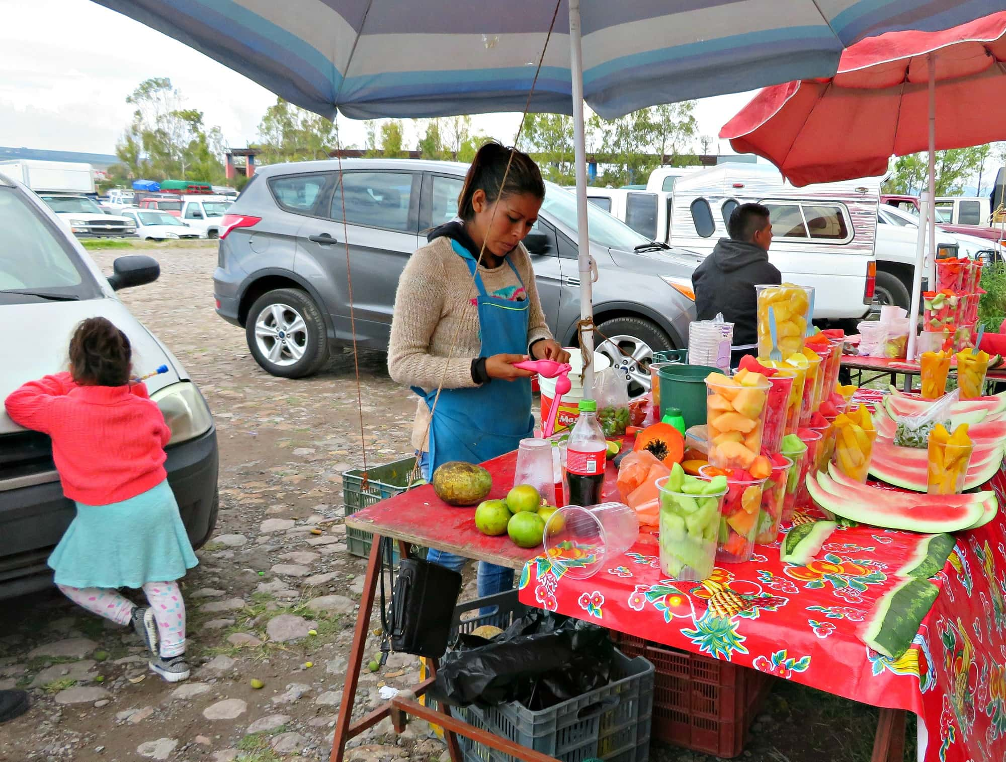 A vendor selling fresh fruits at Tuesday Market in San Miguel de Allende with kids