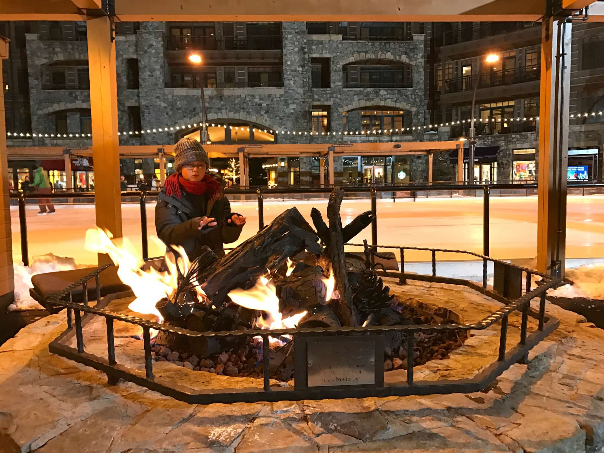 My son warming up by the fire at the ice rink in the Village at Northstar