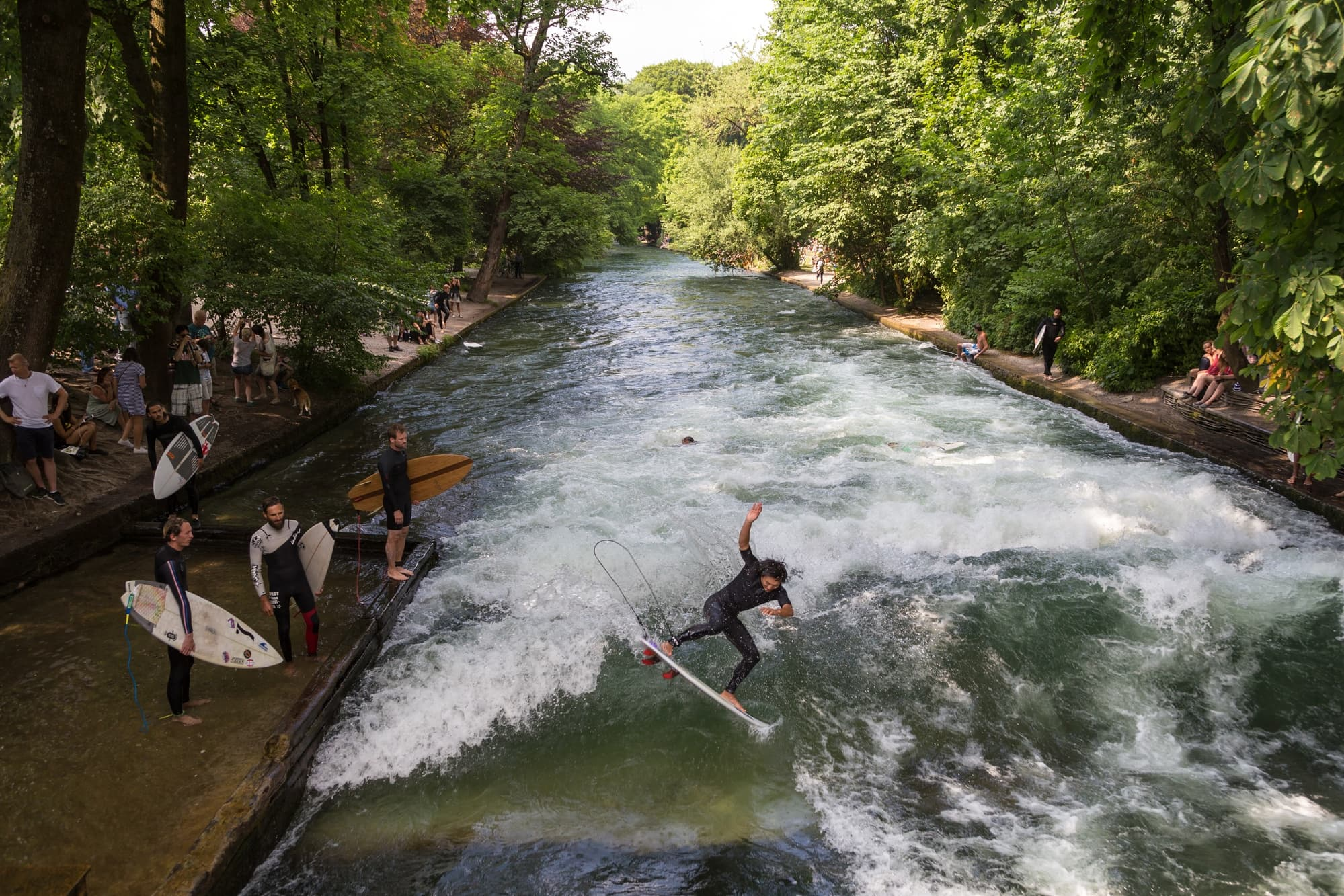 A German surfer hanging ten in the Eisbach River ~ Munich with kids