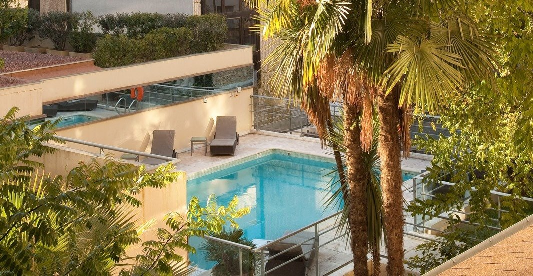 Oceania Le Metropole Montpellier features a palm-lined pool