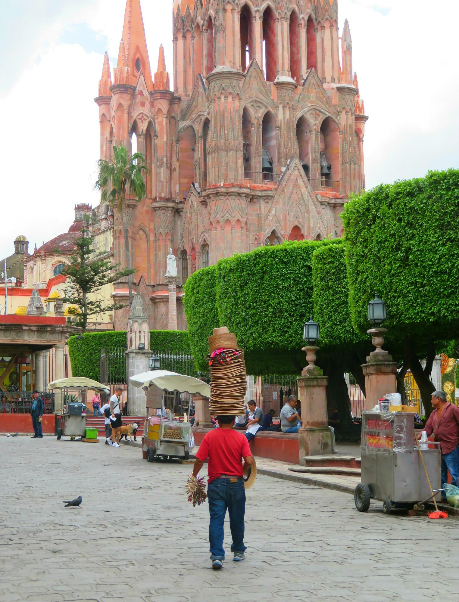 A hat vendor wanders through San Miguel de Allende's central square