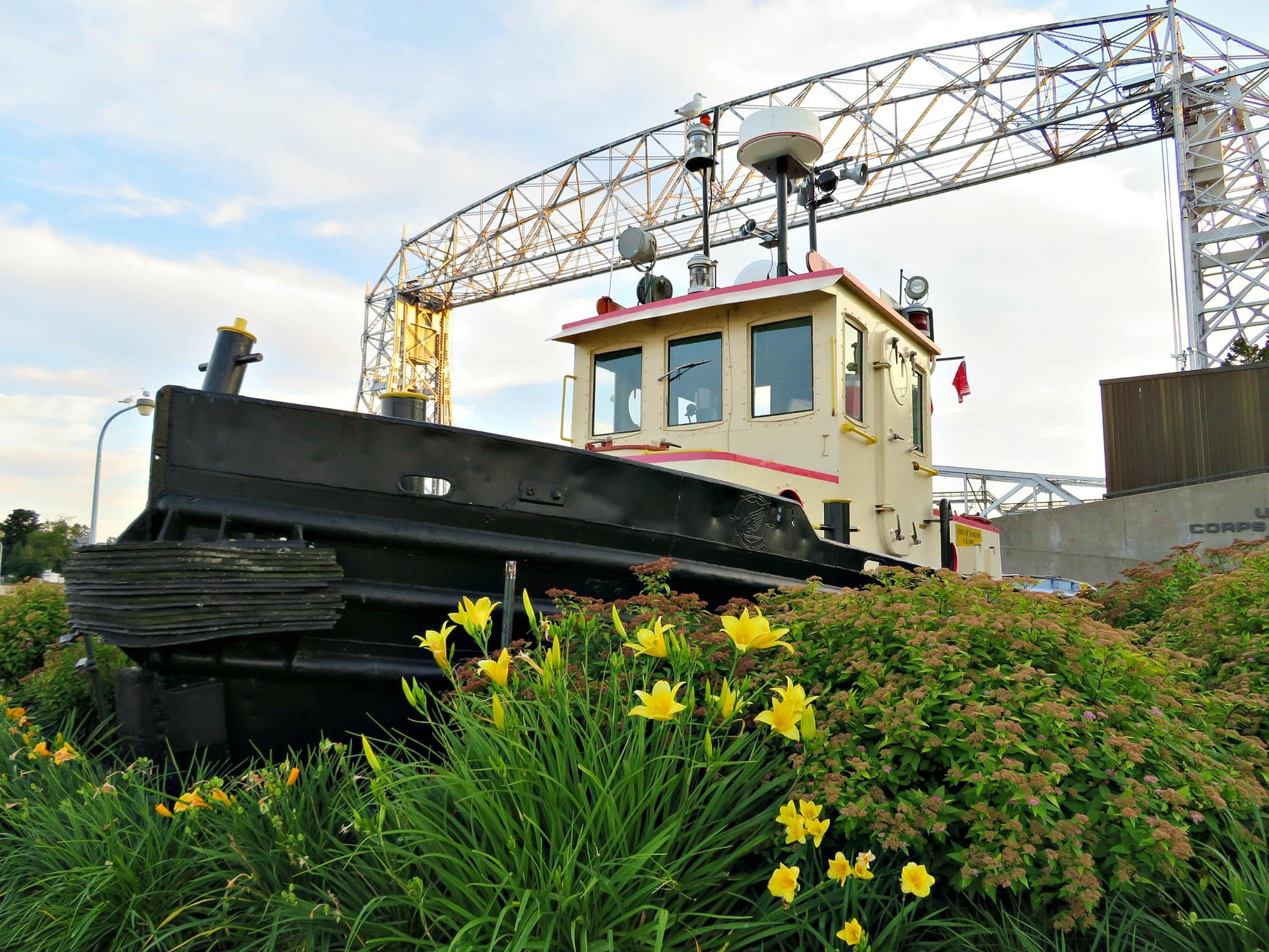 A boat on display in Canal Park with the Aerial Bridge in the distance