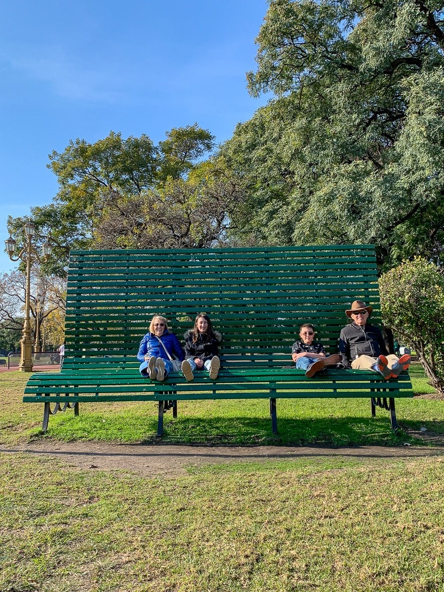 Kids sitting with grandma and grandpa on a huge park bench in Buenos Aires