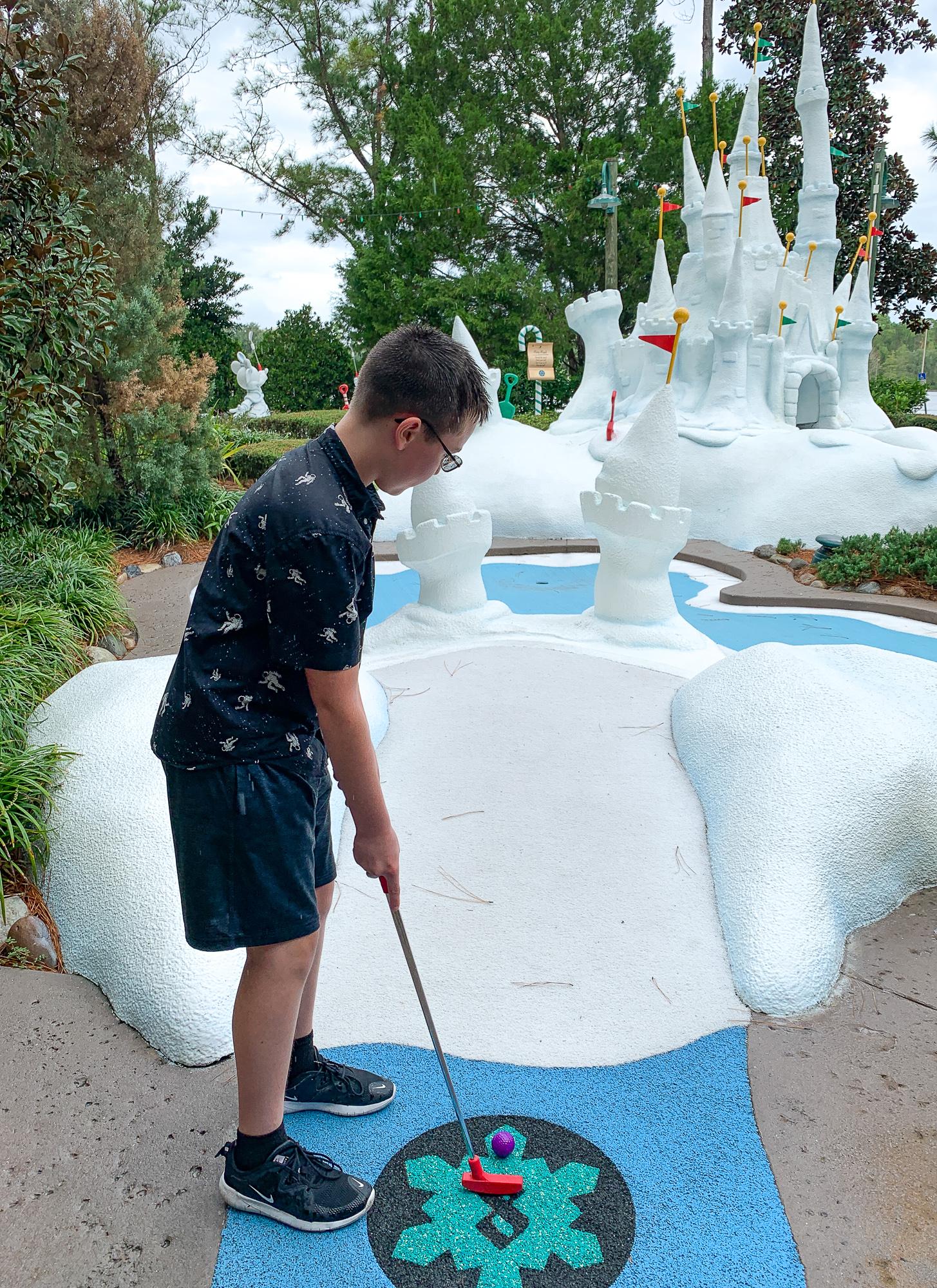 Tween playing putt putt at Disney's Winter Summerland Miniature Golf