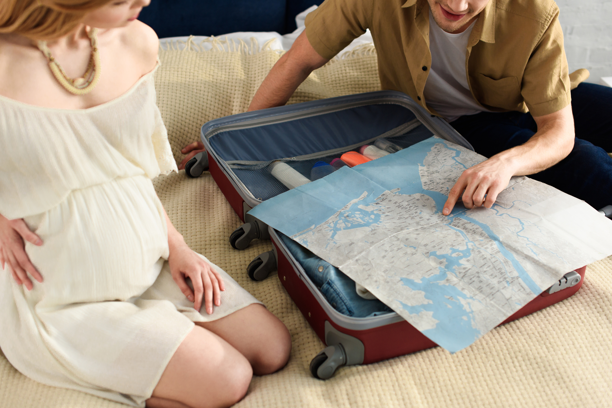 Couple packing for a babymoon vacation