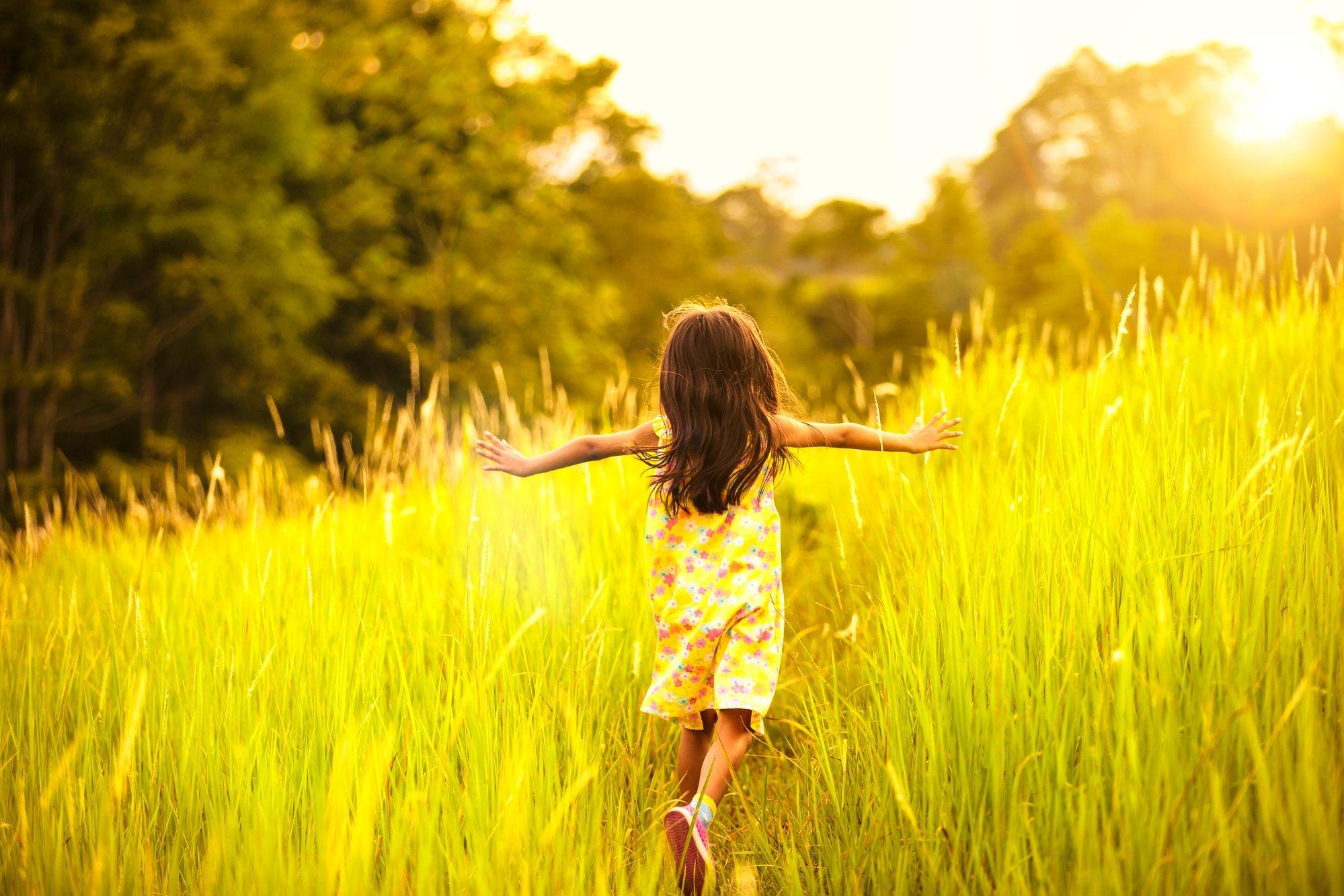 Little girl running though meadow