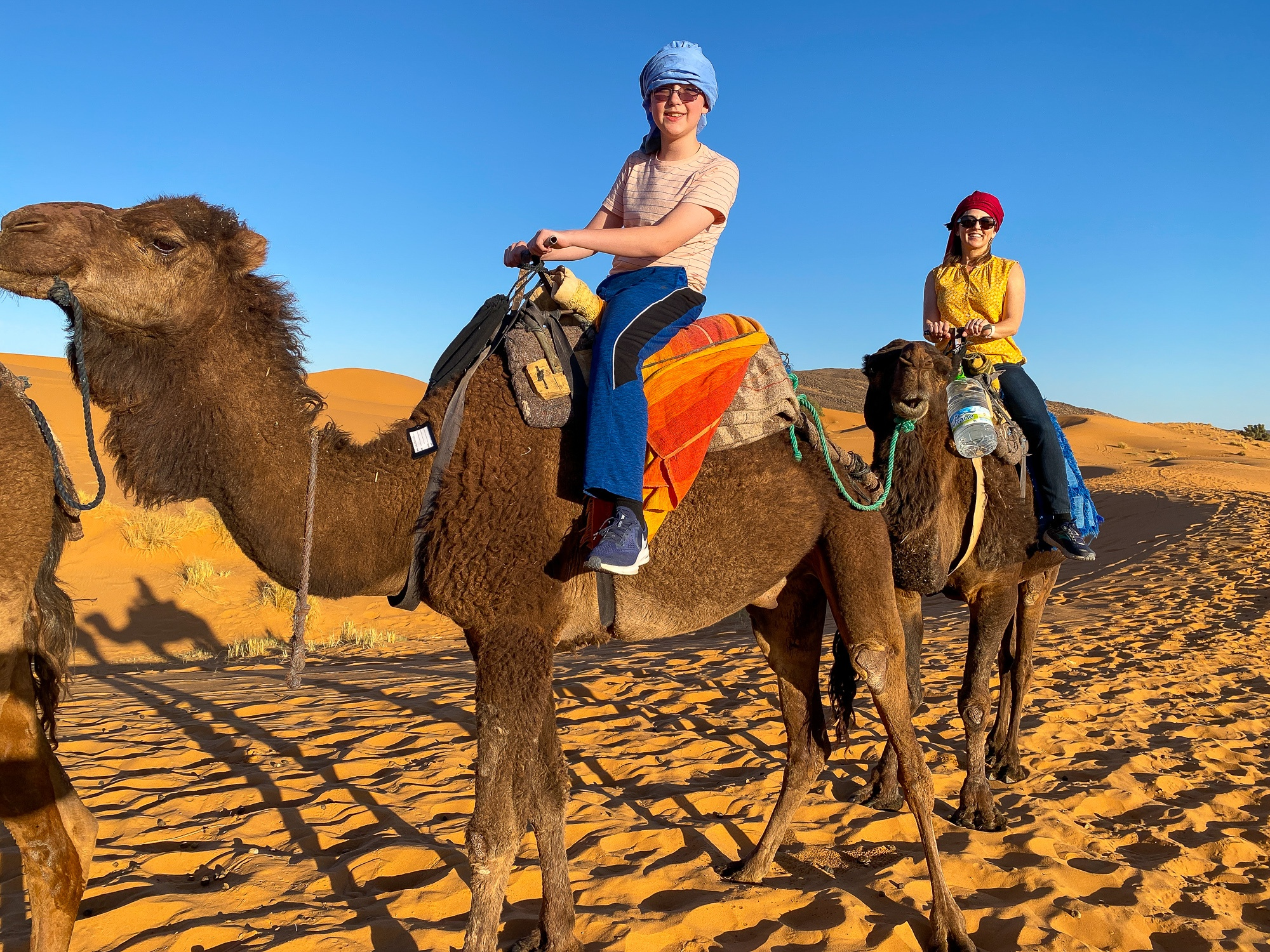 Son and mom atop dromedaries in the Saharan Desert in Morocco