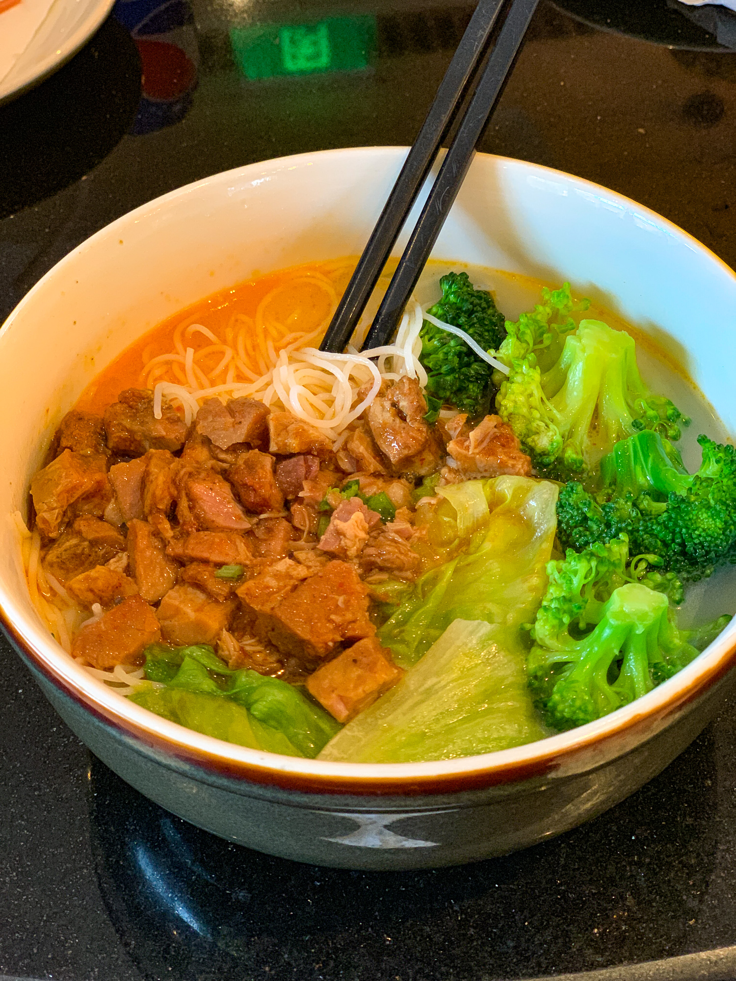 Breakfast soup with spicy pork, rice noodles, broccoli and bok choi from the Dining Room restaurant in Disneytown