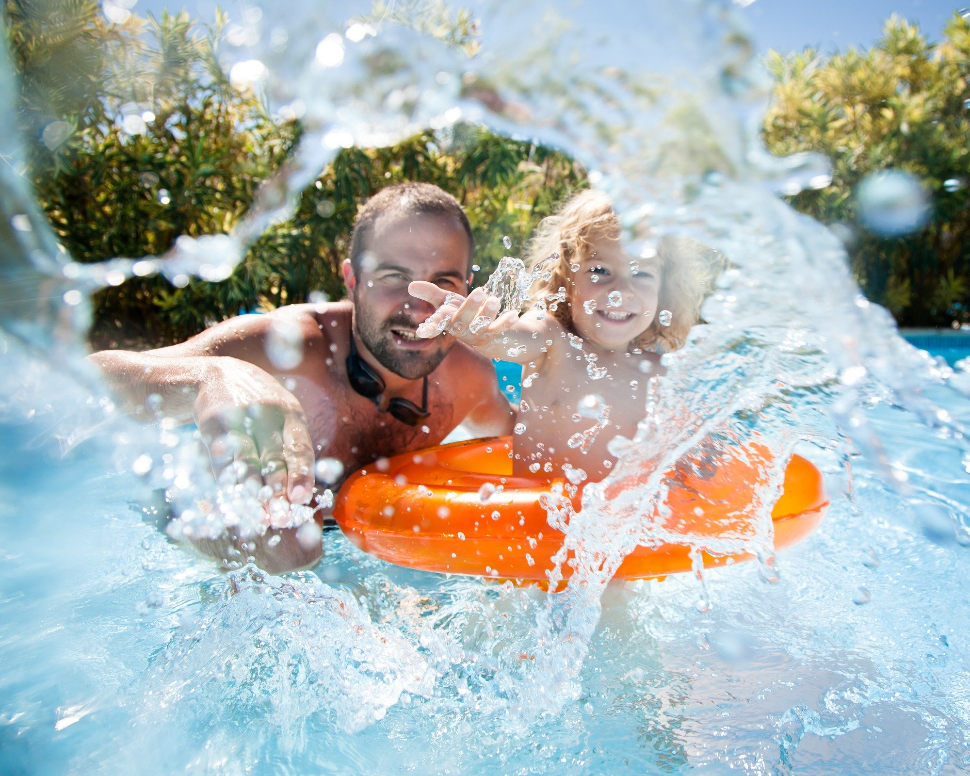 Dad and child swimming together on vacation