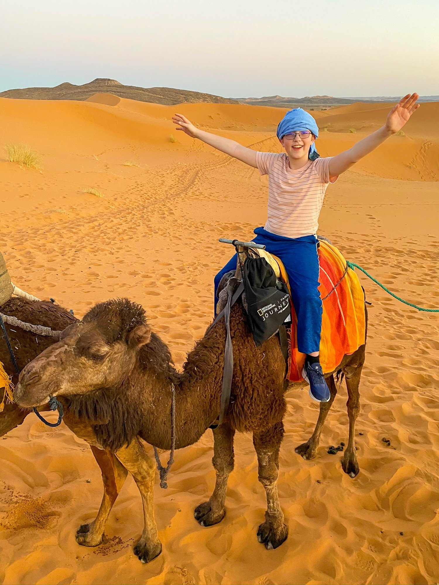 Tween boy on a camel in the Sahara Desert in Morocco