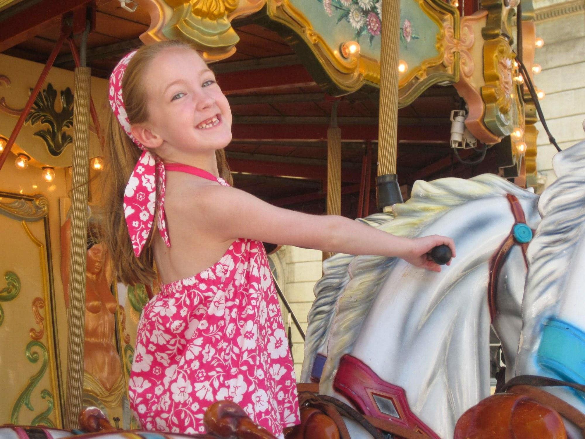Little girl riding carousel in Provence, France