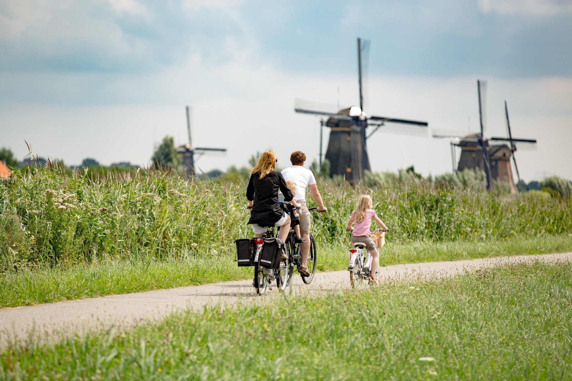 Parents and their child riding bikes near the famous windmills of Kinderdijk in the Netherlands