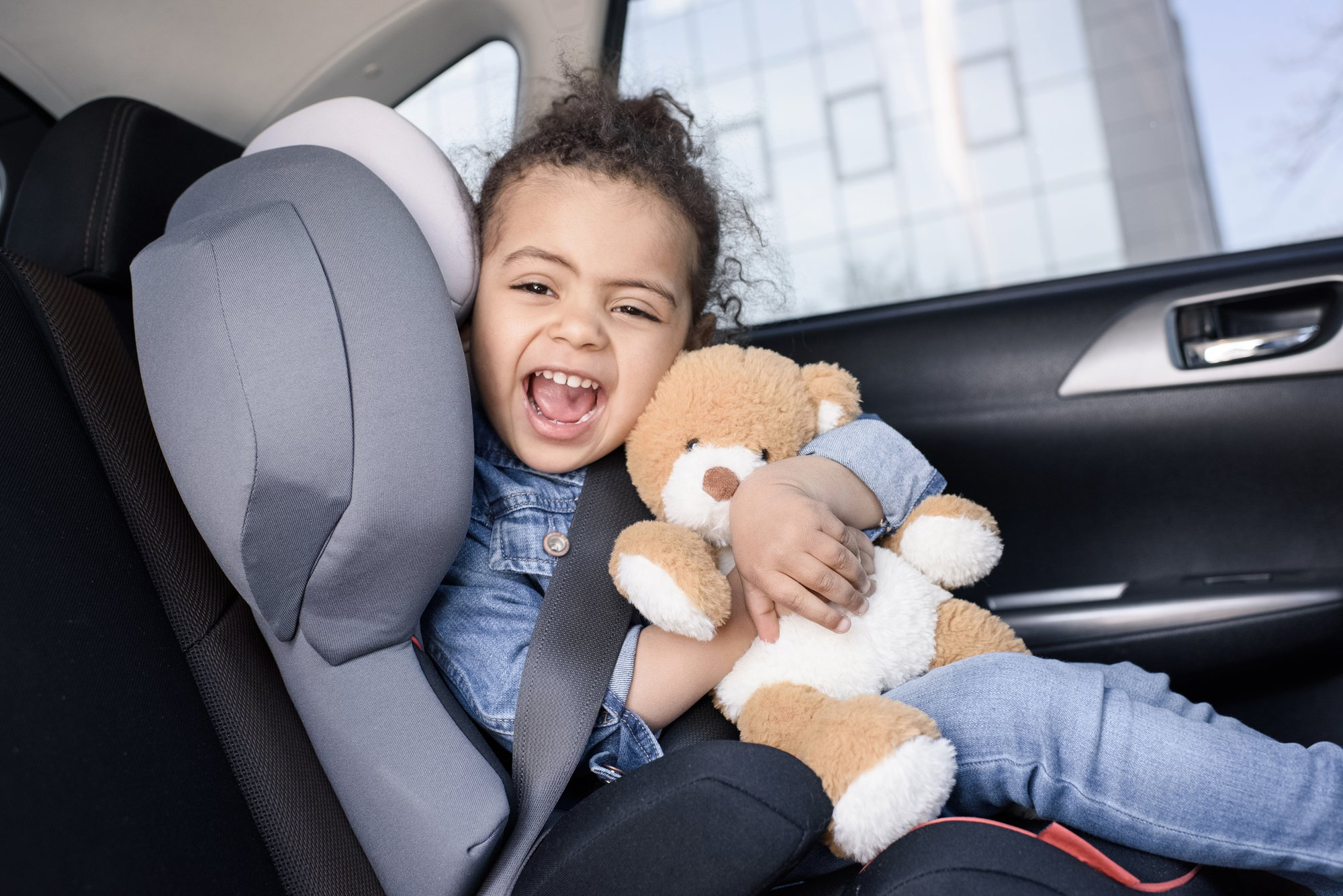 Little girl with toy in car