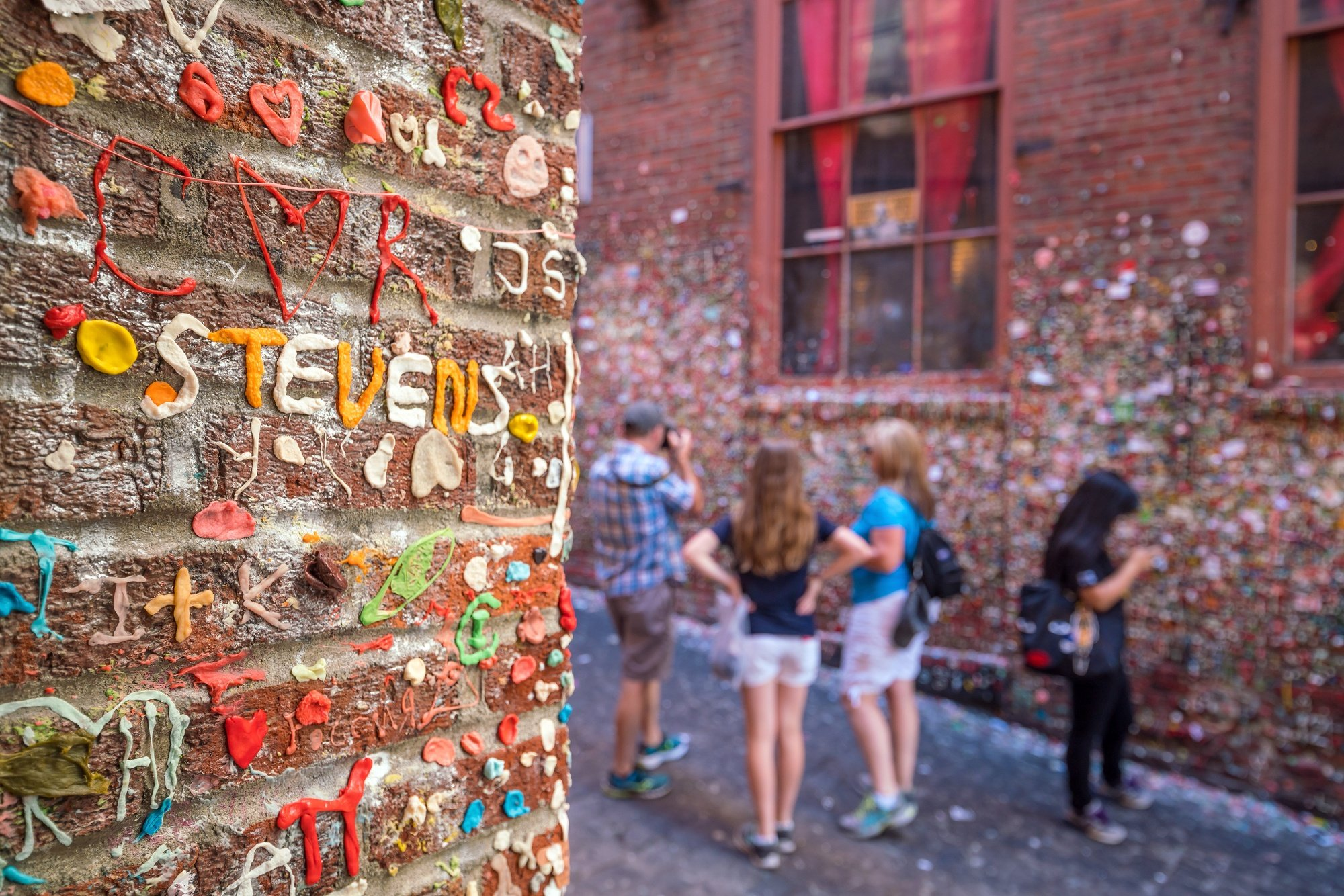 Family exploring the Market Theater Gum Wall in Seattle on vacation
