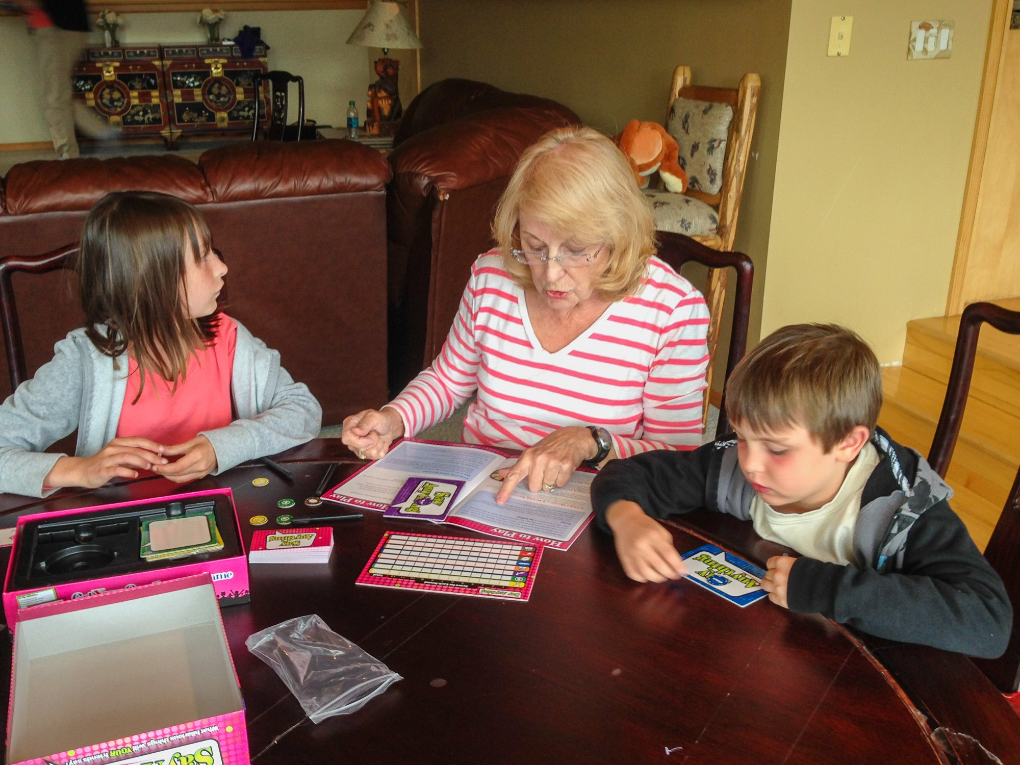 Grandma and kids playing board game together on family reunion vacation