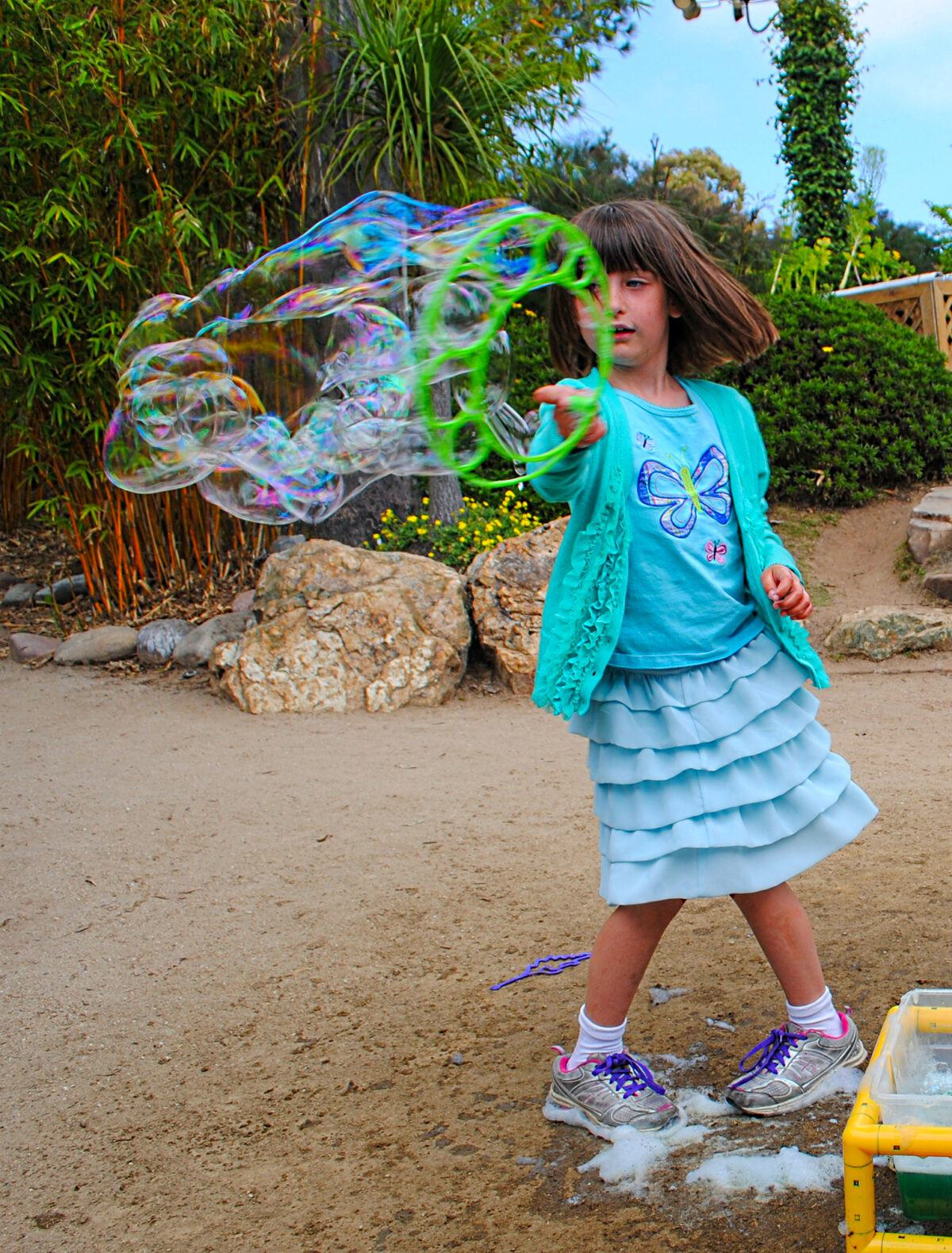 Child making bubbles in the Seeds of Wonder Garden