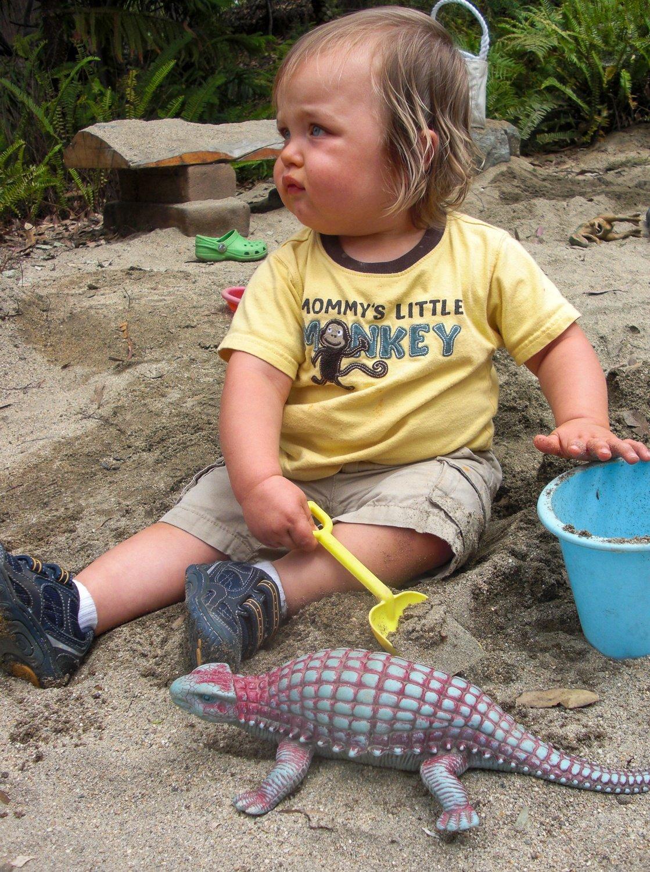 Toddler digging for dinosaurs in the Seeds of Wonder Children's Garden